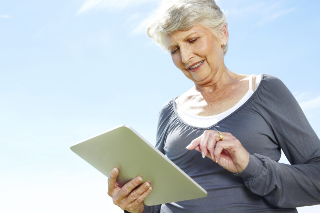 Senior woman using a tablet application outdoors.