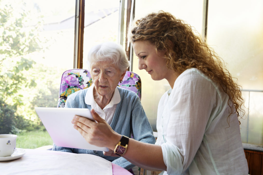 Senior woman and her caregiver lokk at a tablet PC together