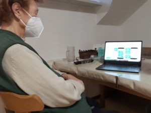 Elderly woman looking at illustrations of smartphone screens.